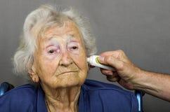 Пожилой гражданин имея температуру быть проверенным Стоковое Изображение