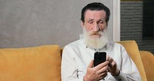 Пожилой гражданин использует смартфон акции видеоматериалы