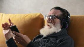 Пожилой гражданин поя в наушниках сток-видео