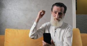 Пожилой гражданин преуспевает в использовании смартфона сток-видео