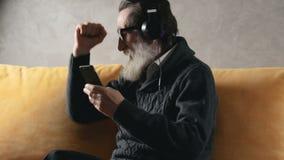 Пожилой гражданин слушает музыку видеоматериал
