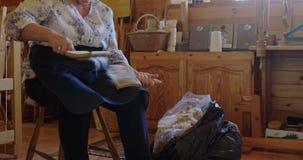Пожилой гражданин чистя шерстяную пульпу щеткой потока с щетками 4k сток-видео