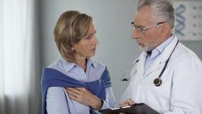 Пожилой доктор говоря к женскому пациенту показывая результаты, заболевание, путь обработки акции видеоматериалы