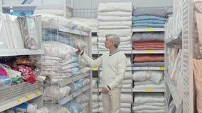 Пожилой мужской клиент выбирая магазин товаров постельных принадлежностей дома видеоматериал
