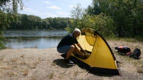 Пожилой мужчина выбыл туриста положил спальный мешок в шатер Зеленый туризм, сток-видео