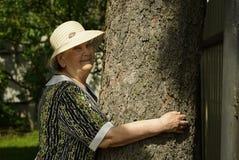 Пожилой обнимая ствол дерева ее руки в лесе Стоковые Фотографии RF