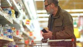 Пожилой пенсионер человека с серой бородой и стеклами комплектует вне сыр в супермаркете и кладет его в тележку молокозавод сток-видео