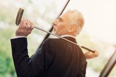 Пожилой респектабельный человек представляя в его офисе с гольф-клубом Он сидит на настольном компьютере за компьтер-книжкой стоковое фото