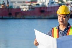 Пожилой, средний - достигший возраста инженер человека азиатов с желтым шлемом и голубой рубашкой наблюдает проект в листе около стоковая фотография
