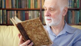 Пожилой старший человек ослабляя дома книгу чтения наслаждаясь выходом на пенсию Книжные полки на заднем плане видеоматериал