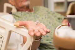 Пожилой стационарный больной держа руку вне Стоковые Изображения RF