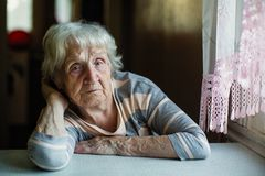 Пожилой унылый пенсионер женщины сидит уныло около окна стоковое фото rf