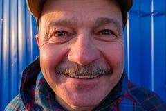 Пожилой человек в взглядах и улыбках бейсбольной кепки на предпосылке Стоковые Фотографии RF