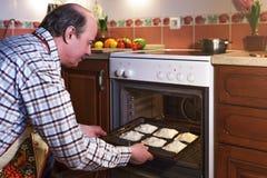Пожилой человек в рисберме подготавливает пироги Стоковые Изображения RF