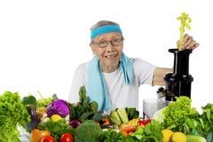 Пожилой человек делая vegetable сок на студии стоковые изображения