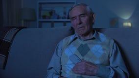 Пожилой человек держа удаленный регулятор спать перед ТВ, вечером дома видеоматериал