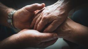 Пожилой человек держит руки его пожилой жены в его сильных, трудясь ладонях Пожилой один другого влюбленности пар несмотря на вре Стоковое Изображение RF