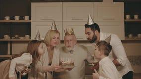 Пожилой человек дует вне свечи на торте акции видеоматериалы
