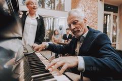 Пожилой человек играет рояль Доктор на голове таблицы стоковое изображение