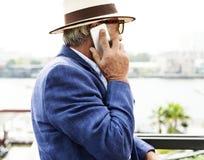 Пожилой человек использует мобильный телефон Стоковое Фото