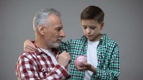 Пожилой человек кладя монетку в копилку мальчика, сбережения на будущее, банк видеоматериал