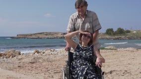 Пожилой человек носит его жену в кресло-коляске вдоль прогулки видеоматериал