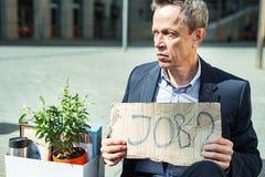 Пожилой человек нося голубую рубашку держа знак пока ищущ занятость стоковое изображение