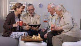 Пожилой человек показывая друзьям новый проект на ПК планшета, тормозе игры шахмат, компании сток-видео