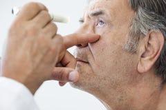 Пожилой человек расмотренный офтальмологом Стоковая Фотография RF