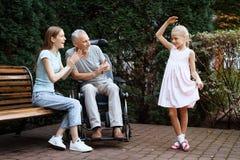Пожилой человек сидит в кресло-коляске Он увиден женщиной с девушкой Они сидят на стенде в парке Стоковая Фотография RF