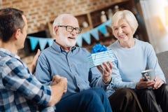 Пожилой человек смотря подарок на день рождения от его семьи стоковые изображения rf