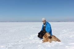 Пожилой человек с бородой в синем пиджаке и собаке Лабрадор o стоковые изображения