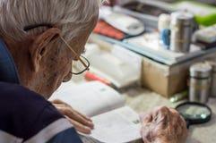 Пожилой человек с стеклами читая сочинительства в тетради около окна дома стоковое фото