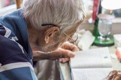 Пожилой человек с стеклами читая сочинительства в тетради около окна дома стоковое изображение rf
