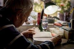 Пожилой человек с стеклами читая сочинительства в тетради около окна дома стоковые фотографии rf