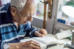 Пожилой человек с стеклами читая сочинительства в тетради около окна дома стоковые изображения