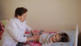Пожилой masseur женщины делая массаж брюшка к маленькой девочке в больнице сток-видео