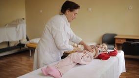 Пожилой masseur женщины делая массаж брюшка к маленькой девочке в больнице видеоматериал