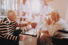 пожило Пациент на кресло-коляске Игра шахмат стоковое изображение rf