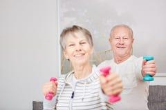 Пожилые гражданины делают спорт дома Стоковое Изображение