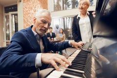 Пожилые люди укомплектовывают личным составом игры рояль в доме престарелых стоковое фото