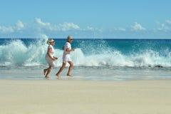 Пожилые пары бежать на пляже Стоковое фото RF