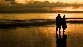 Пожилые пары идя на пляж в заходе солнца Стоковые Фотографии RF