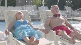 Пожилые положительные пары лежа на sunbeds около бассейна держа руки и усмехаться r Остатки в гостинице акции видеоматериалы