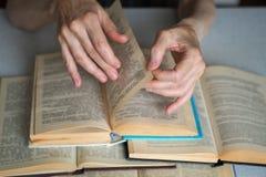 Пожилые руки с раскрытыми книгами, конец человека вверх, выбранный фокус, нерезкость стоковая фотография