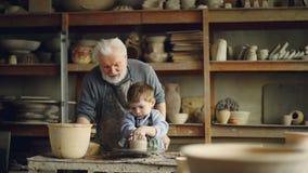 Пожилым гончар испытанный человеком учащ мальчику как работать с глиной на колесе ` s гончара делить опыта сток-видео