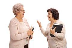 2 пожилых женщины при книги имея переговор стоковое изображение