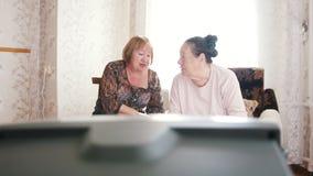 2 пожилых женщины смотря ТВ, комментируя и говоря друг к другу акции видеоматериалы