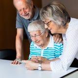 3 пожилых люд используя умный телефон стоковые фото