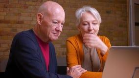 2 пожилых седых кавказских супруга связывают в videochat на ноутбуке обнимая нежно один другого акции видеоматериалы